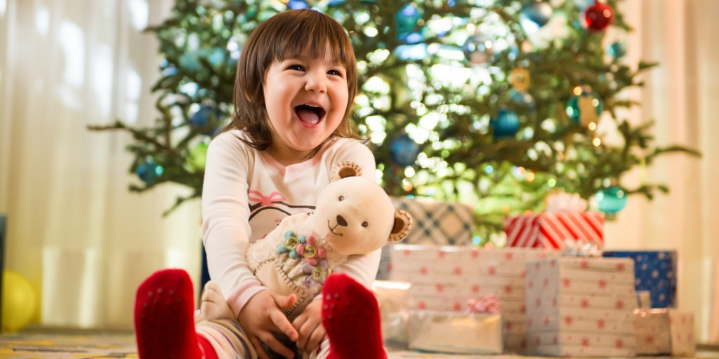 Girl laughing by Christmas tree